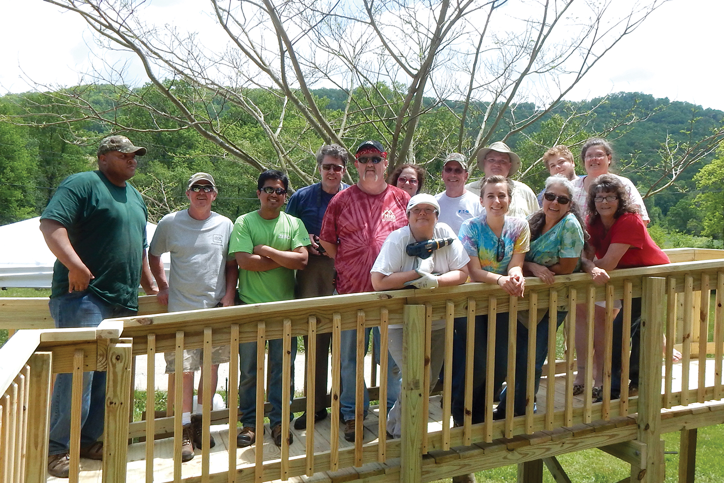 A group of MHO volunteers smile as they build.